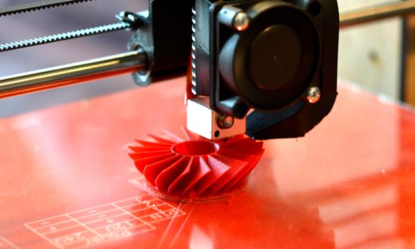 3D printer printing an orange fan-like component.