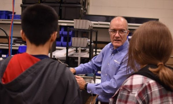"Nick Hackett, President of New Way Air Bearings, shows students from the ""What's So Cool About Manufacturing?"" competition the intricacies of one of the manufacturing machines at New Way Air Bearings."