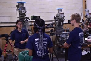 New Way Air Bearings' intern from Drexel University, Lauren Lugones, demonstrates to two E.T.Richardson Middle School students how one piece of manufacturing equipment at New Way works to create Porous Media Air Bearings.