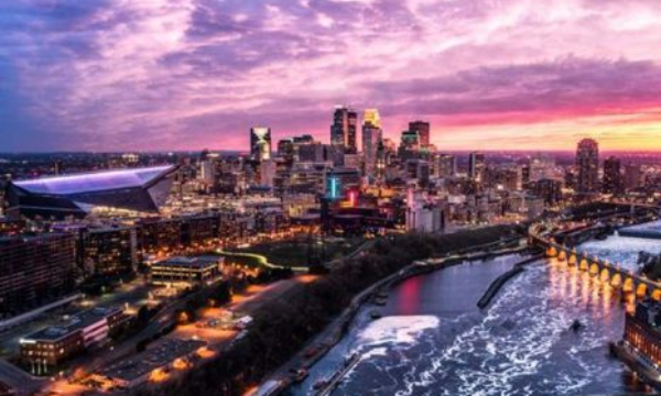 Minneapolis, Minnesota cityscape and river with a pink and purple sunset.