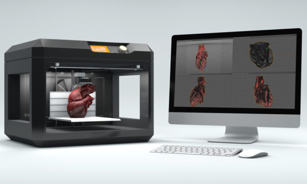 An example of a 3D printed heart inside a 3-D printing device next to a desktop computer displaying the human heart.