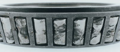 Close up image of a roller bearing with heavy spalling damage on the individual roller surfaces