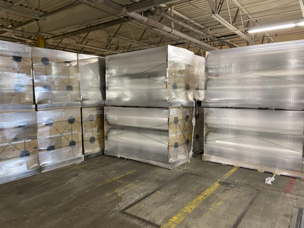 Warehouse holding several large rolls of polystyrene.
