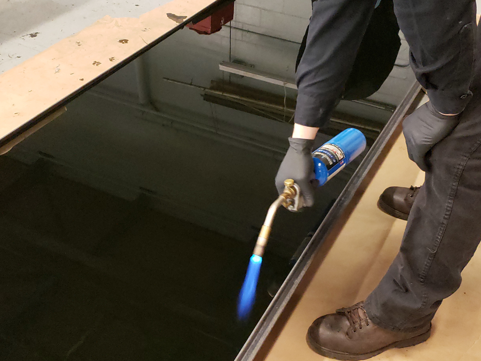 Technician utilizing torch to pop bubbles on epoxy surface.
