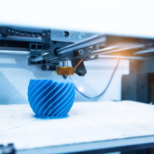 3D printer manufacturing a spiraling blue object.