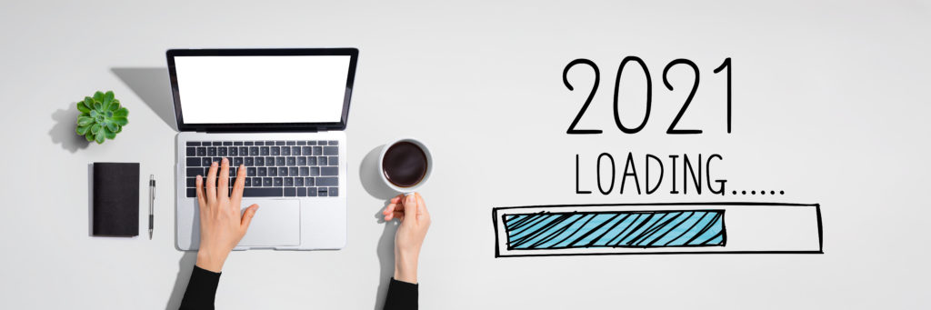 """Overhead shot of a person's hands with coffee and a laptop, and a graphic of a loading bar with the words """"2021 loading."""