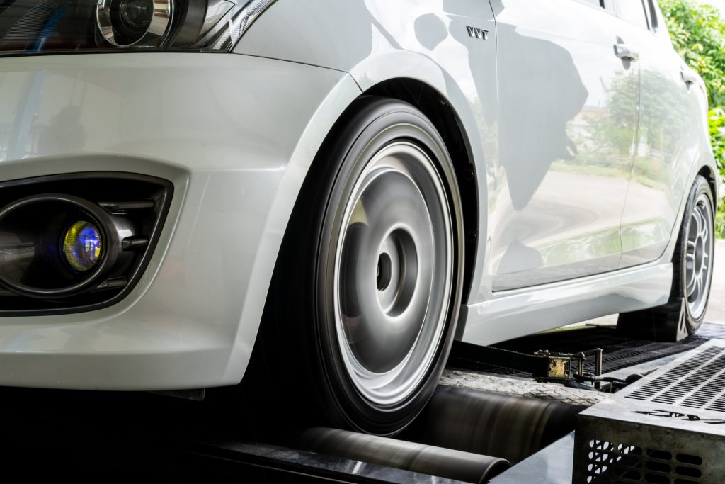 A car with front-wheel drive performs a dynamometer test in an open garage.