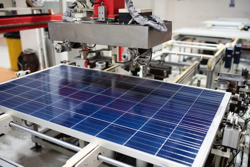 A solar panel sits on a mechanical platform for automated assembly.