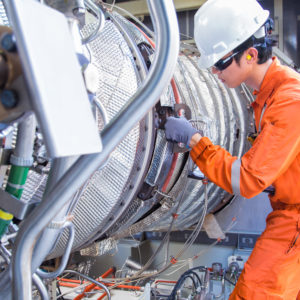 Turbine technician wearing personal protective equipment inspects a gas turbine engine