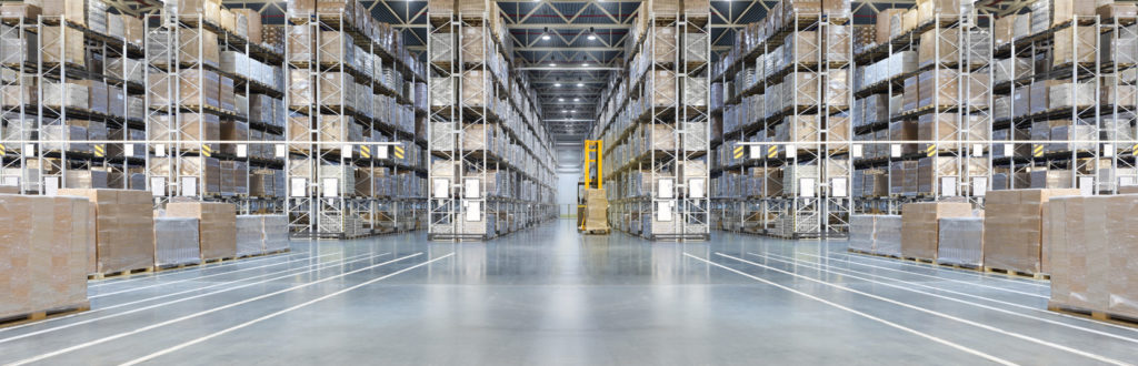 Huge distribution warehouse with high shelves and loaders.