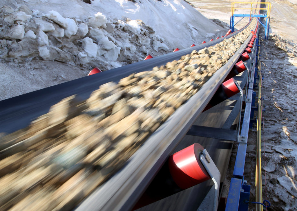Conveyor belt in motion carrying raw materials from a mine.