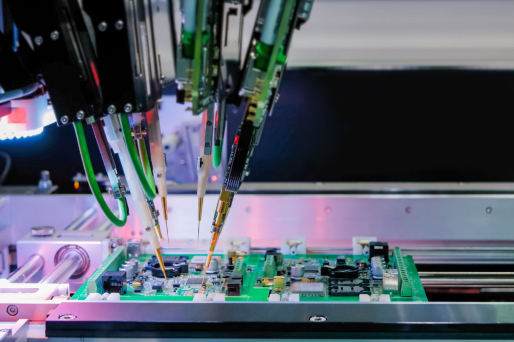 Automated semiconductor manufacturing, robotic arms assembling a circuit board.