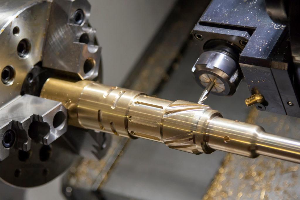 CNC lathe machining a complex part from brass.